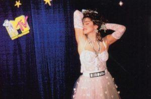 """MADONNA: Madonna da her ne kadar bazen Marilyn Monroe'dan esinlense de tıpkı Michael Jackson gibi kendi modasını yaratan ve başta Lady Gaga olmak üzere kendisinden sonra çıkan birçok kadın şarkıcı tarafından taklit edilen bir isim... Vogue'daki kostümlerini kim unutabilir mesela? Fakat sanıyorum en bilineni MTV Müzik Ödülleri'nde ilk kez canlı yayında sahneye çıktığı """"Like a Virgin"""" performansında giydiği gelinlik olabilir. Kollarına kadar uzayan beyaz eldivenlerini, """"Boy Toy"""" yazan kemerini, inci kolyelerini, büyük yıldızlı küpelerini, permalı sarı saçlarını kim unutabilir ki? 80'li yıllarda tüm kızlar da öyle giyiniyordu. Hatta hiç unutmam, seyyar satıcılar """"Madonna bilezikleri bunlar"""" diye renkli bileklikler satıyordu."""